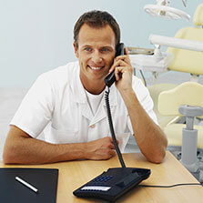 man in a dental office sits at a table and holds a phone up to his ear