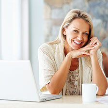 blonde woman sits at a table with a laptop and mug in front of her and she smiles widely
