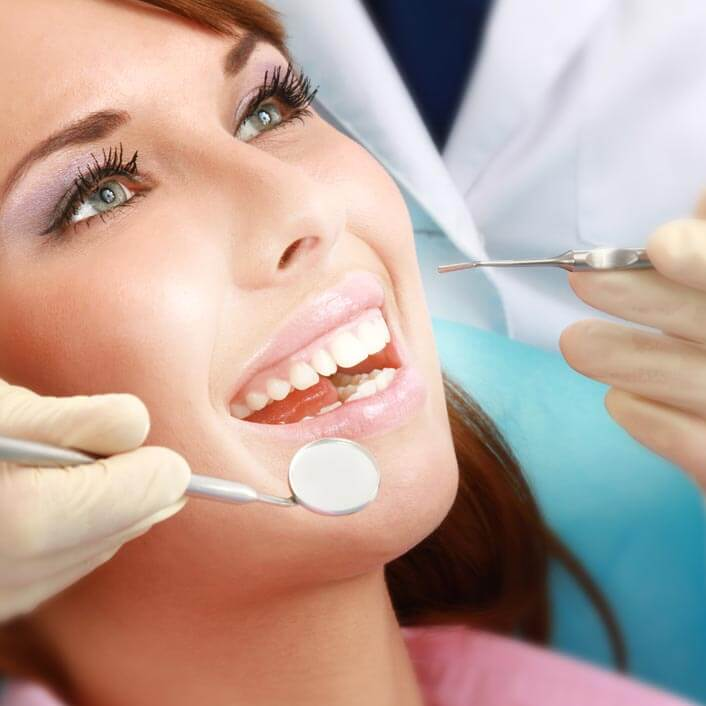 close up of a woman's face as she lays in the dental chair getting her teeth looked at by the dentist