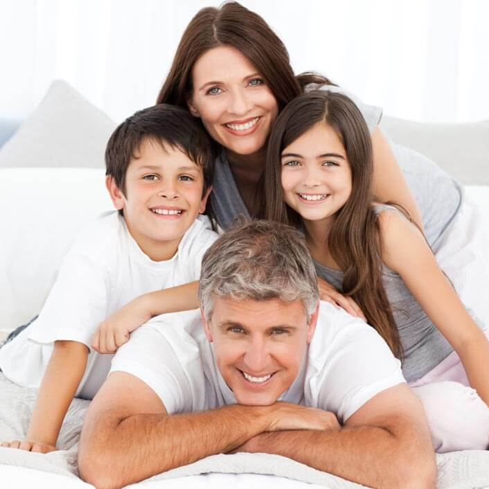a family with a father, mother, boy, and girl lay on a bed smiling