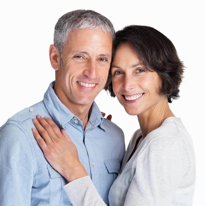 A husband and wife embrace and smile at the camera
