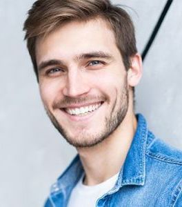 man with brown hair smiles at the camera