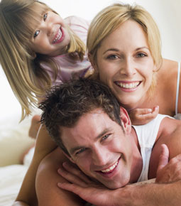 a family with a father, mother, and little girl lay on top of each other smiling