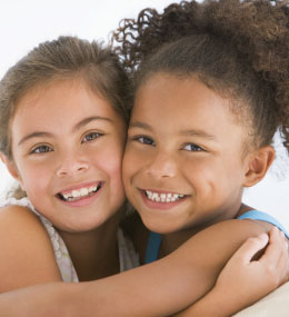 two young girls hug each other and smile at the camera