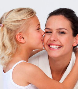 photo of a little girl with blonde hair kissing her mother on the cheek as she smiles