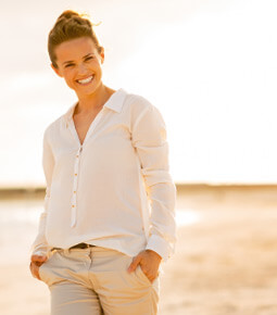 woman wearing light colored clothes stands outside and smiles with her hands in her pants pockets