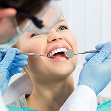 close up of a girl laying in a dental chair as the dentist looks at her teeth