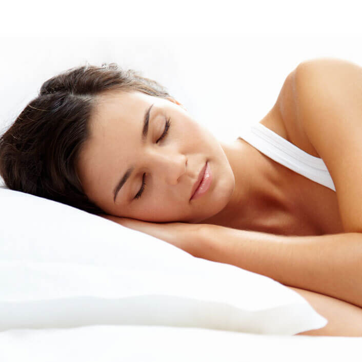 woman with dark hair sleeping on her side in a white bed