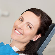 smiling face of a woman with dark hair laying in a dental chair